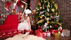 Het meisje vond giften onder Kerstboom, kiest de dochter in het kostuum van de Elfkerstman ` s verrassing voor Nieuwjaar, Kerstmi stock videobeelden