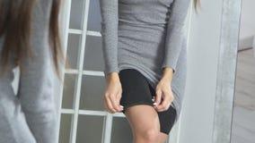 Het meisje voor een spiegel kleedt een kleding stock videobeelden