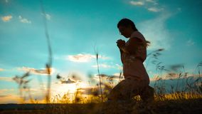 het meisje vouwde haar indient gebedsilhouet bij zonsondergang langzame geanimeerde video Het meisje vouwde haar indient gebed bi stock videobeelden