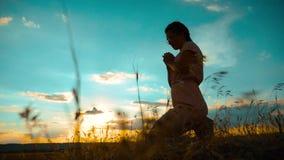 het meisje vouwde haar indient gebedsilhouet bij zonsondergang langzame geanimeerde video Het meisje vouwde haar indient gebed bi stock footage