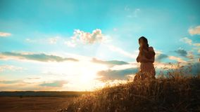 het meisje vouwde haar indient gebedsilhouet bij zonsondergang levensstijlvrouw die op haar knieën bidden langzame geanimeerde vi stock video