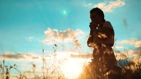 het meisje vouwde haar indient gebedsilhouet bij zonsondergang vrouw die op haar knieën bidden langzame geanimeerde video Het mei stock videobeelden