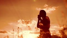 het meisje vouwde haar indient gebedsilhouet bij zonsondergang vrouw die op haar knieën bidden langzame geanimeerde video Het mei stock video