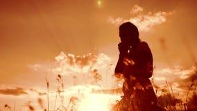 het meisje vouwde haar indient gebedsilhouet bij zonsondergang vrouw die op haar knieën bidden langzame geanimeerde video Het mei stock footage