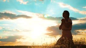 Het meisje vouwde haar indient het silhouet van het levensstijlgebed bij zonsondergang vrouw die op haar knieën bidden langzame g stock videobeelden