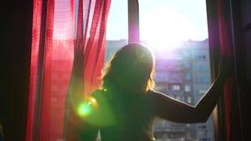 Het meisje vroege ochtend loopt aan het venster en opent het De zon` s stralen gaan door het glas over, verlichten de ruimte en stock videobeelden