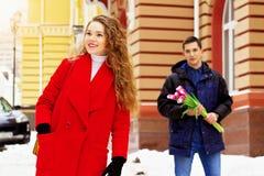 Het meisje wacht op haar vriend, die zich met bloemen achter haar bevindt Jong paar die samen in de stad lopen royalty-vrije stock foto's