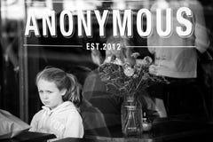Het meisje wacht op orde alleen bij een koffie kijkend droevig en alleen royalty-vrije stock afbeelding