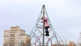 Het meisje in warme kleren beklimt en hangt op speelplaats stock footage