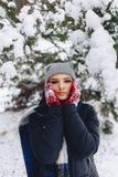 Het meisje warmes haar wangen in handschoenen bij de koude winter in p stock afbeelding