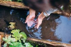 Het meisje wast haar indient bronwater stock foto's