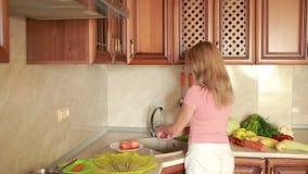 Het meisje wast perziken Groenten op de keukenlijst Handen die mes houden stock footage