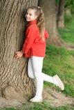 Het meisje weinig leuk kind geniet van vrede en kalmte bij boomboomstam Rust en vreedzaam Het levenssaldo Vreedzame stemming Goed stock afbeelding