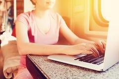 Het meisje werkt aan een laptop computer stock foto's
