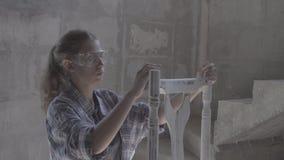 Het meisje werkt in een timmerwerkworkshop, poetsmiddelenmeubilair stock video