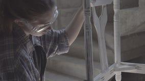 Het meisje werkt in een timmerwerkworkshop, poetsmiddelenmeubilair stock videobeelden