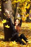 Het meisje werpt bladeren stock foto's