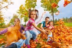 Het meisje werpt de bladeren van de de herfstesdoorn aan camera Stock Fotografie