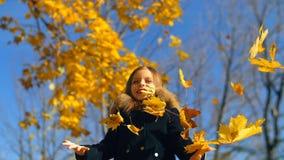 Het meisje werpt omhoog bladeren stock video