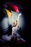 Het meisje werpt op hoofdkussens Stock Foto's