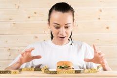 Het meisje wil een hamburger Het meisje is op een dieet de vrouw wil een hamburger eten stock foto