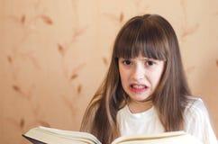 Het meisje wil niet lezen Stock Afbeelding