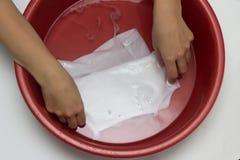 Het meisje wist kinderen ` s de witte T-shirt in een rood bassin van vlekken, van vlekkenmiddel, close-up, handen witte achtergro royalty-vrije stock foto
