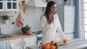 Het meisje in witte badjas eet gesneden appel in keuken, kijkt uit venster, langzame motie stock footage