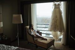 Het meisje in witte damesslipjes en kousen leunt op de stoel royalty-vrije stock fotografie