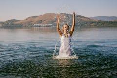 Het meisje in witte kleding baadt in de meerzomer royalty-vrije stock fotografie