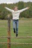 Het meisje in witte sweater en jeans springt van de omheining Levensstijlportret Stock Foto