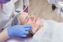 Het meisje wordt aangeboden de schoonmakende dienst van de ultrasone klankhuid in de schoonheidssalon stock afbeeldingen