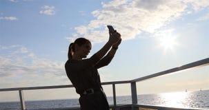 Het meisje wordt gefotografeerd op het dek van het schip stock footage