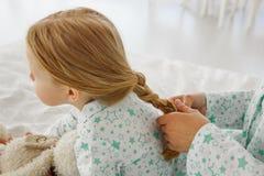 Het meisje wordt gevlecht met een vlecht Het mamma vlecht een vlecht aan haar dochter Maak een kapsel royalty-vrije stock afbeeldingen