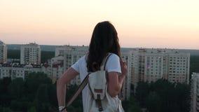 Het meisje zet een rugzak op het dak stock videobeelden
