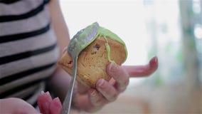 Het meisje zet een zoete groene glans op een kleine cake Close-up van lepels en cakes stock video
