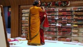Het meisje zet op Sari met Ornament aan Toerist in Winkel stock footage