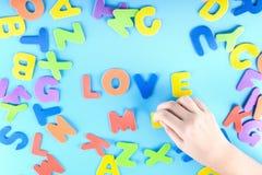 Het meisje zet uit de multicolored brieven de woorden van me houden Mooie achtergrond Royalty-vrije Stock Afbeeldingen