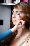 Het meisje zette de make-up op het gezicht Stock Foto