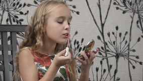 Het meisje zette een lipgloss op lippen voor zakspiegel stock video