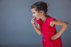 Het meisje zette een vinger in zijn weerzinwekkende mond stock foto