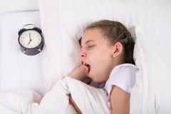 Het meisje zette het horloge op het signaal en ging naar bed stock afbeeldingen