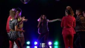 Het meisje zingt in een retro microfoon rond mensen die aan haar dansen die zingen Rook achtergrond Langzame Motie stock video