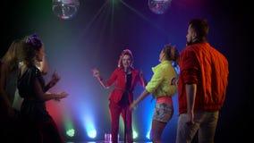 Het meisje zingt in een retro microfoon rond mensen die dansen te zingen Rook achtergrond stock videobeelden