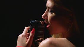 Het meisje zingt in een retro microfoon Zwarte achtergrond Sluit omhoog Zachte nadruk stock footage