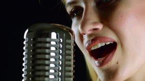 Het meisje zingt in een retro microfoon Zwarte achtergrond Zachte nadruk Sluit omhoog stock videobeelden