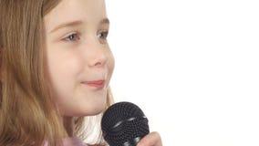 Het meisje zingt het lied in de microfoon Witte achtergrond Sluit omhoog stock videobeelden