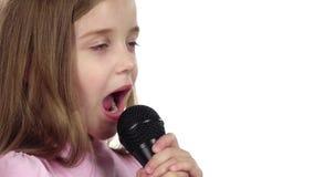 Het meisje zingt het lied in de microfoon Witte achtergrond Sluit omhoog Langzame Motie stock footage