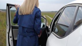 Het meisje zit achter het wiel van een auto stock footage