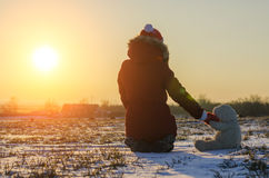 Het meisje zit alleen op de achtergrond van de het plaatsen zon Royalty-vrije Stock Afbeelding